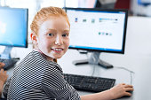Young girl with red hair using computer at elementary school. Happy female child learning to use internet in a computer room. Portrait of young student looking at camera while typing on keyboard.