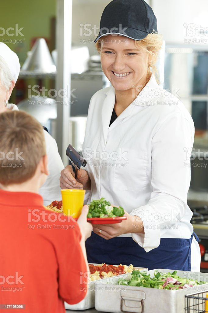 Pupil In School Cafeteria Being Served Lunch By Dinner Lady stock photo