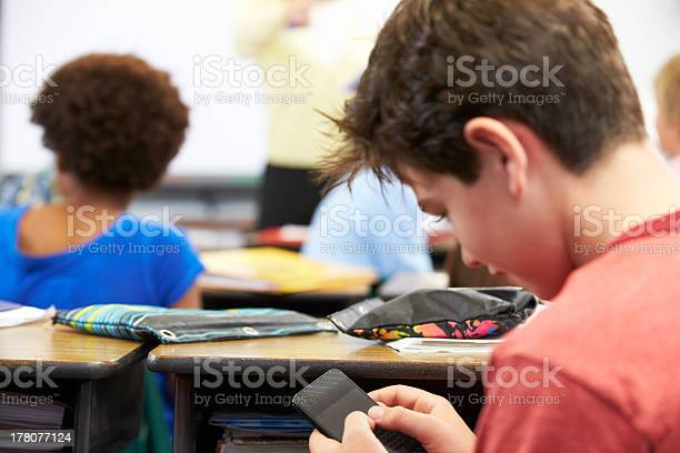 Pupil Sending Text Message On Mobile Phone In Class Stock Photo - Download Image Now