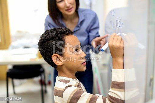 1160928955 istock photo Pupil writing a formula on a whiteboard 1197312676