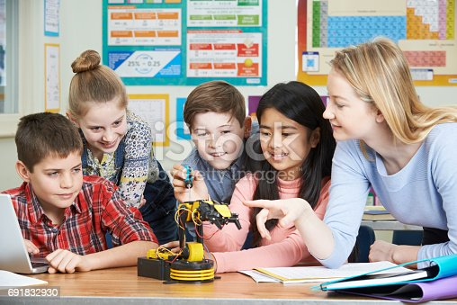 1016655140 istock photo Pupils And Teacher In Science Lesson Studying Robotics 691832930