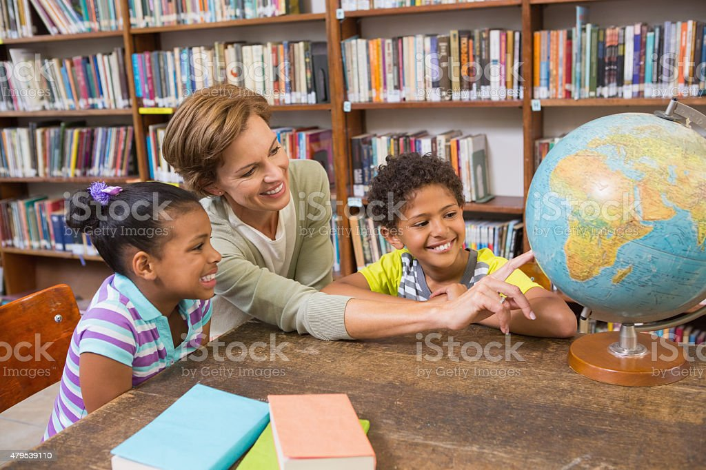 Pupils and teacher looking at globe in library stock photo