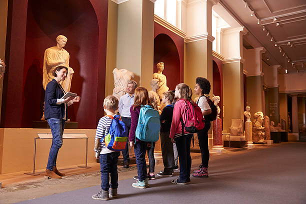 pupils and teacher on school field trip to museum - guide stockfoto's en -beelden