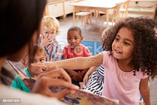 istock Pupils At Montessori School Looking At Book With Teacher 684061930