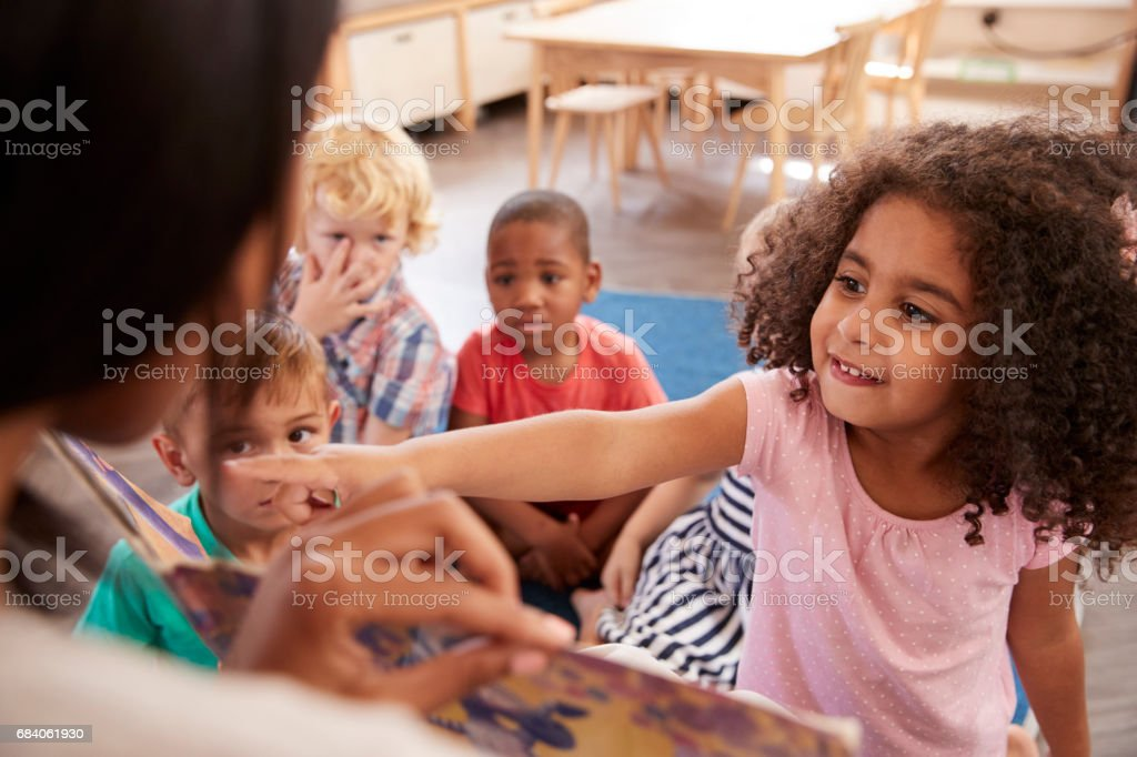 Pupils At Montessori School Looking At Book With Teacher stock photo