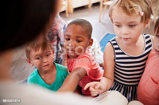 istock Pupils At Montessori School Looking At Book With Teacher 684061974