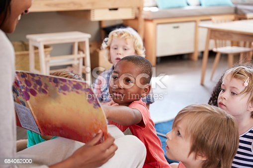 istock Pupils At Montessori School Looking At Book With Teacher 684062000