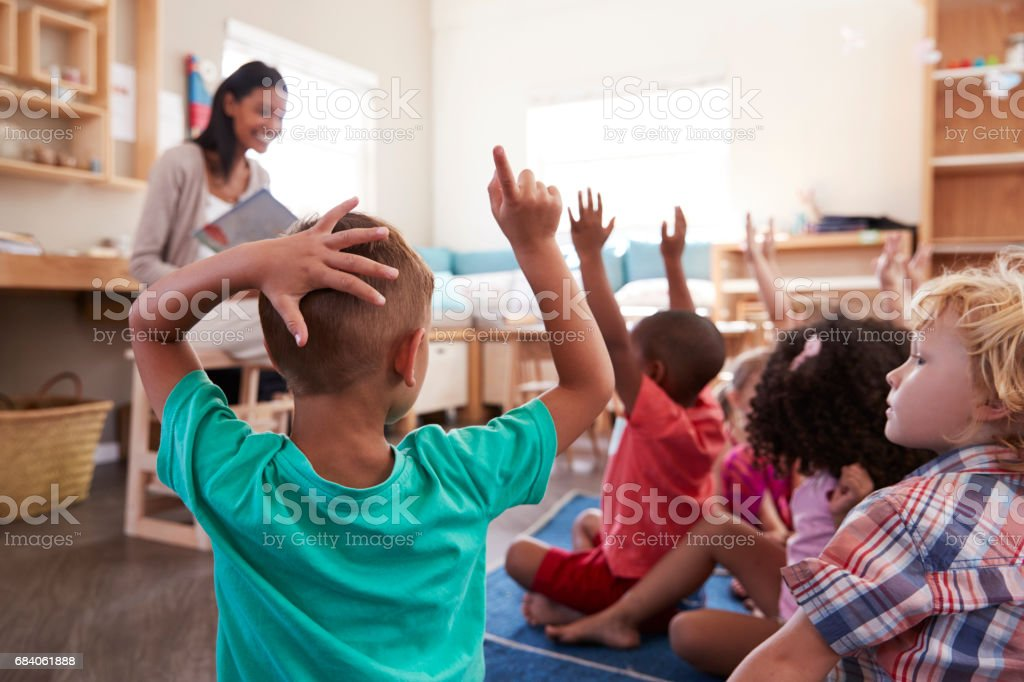 Pupils At Montessori School Raising Hands To Answer Question - foto stock