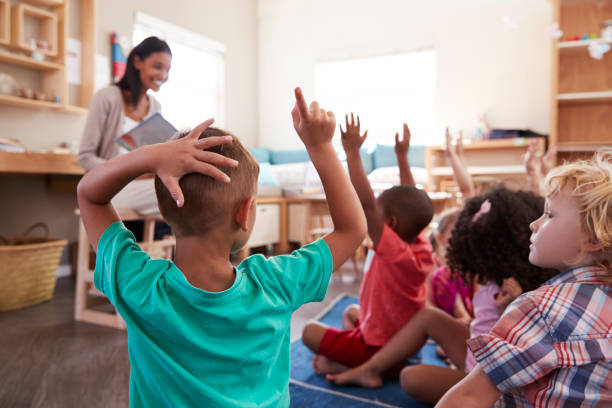 Pupils At Montessori School Raising Hands To Answer Question Pupils At Montessori School Raising Hands To Answer Question preschool age stock pictures, royalty-free photos & images