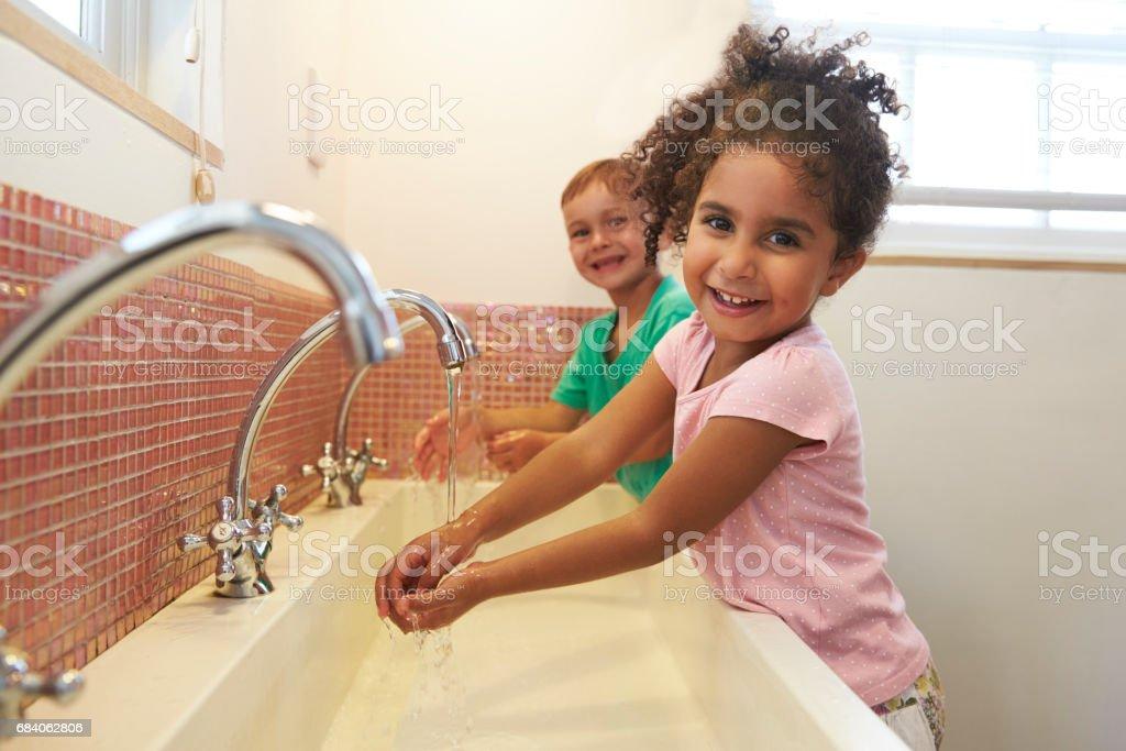 Pupils At Montessori School Washing Hands In Washroom stock photo