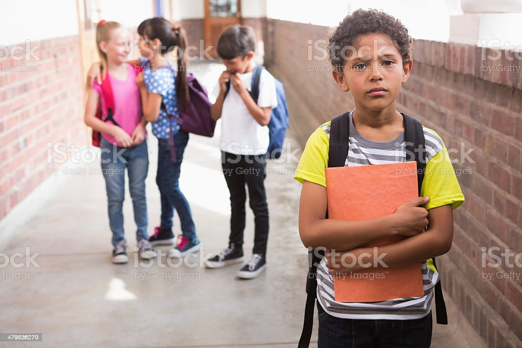 Pupils friends teasing a pupil alone stock photo