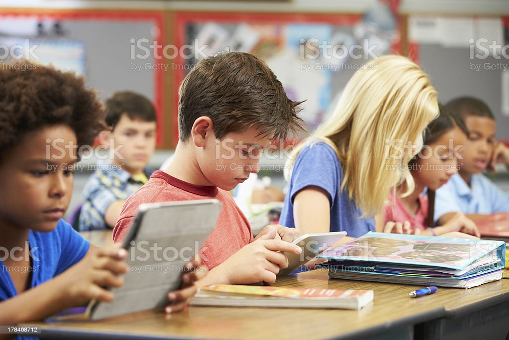 Pupils In Class Using Digital Tablet stock photo