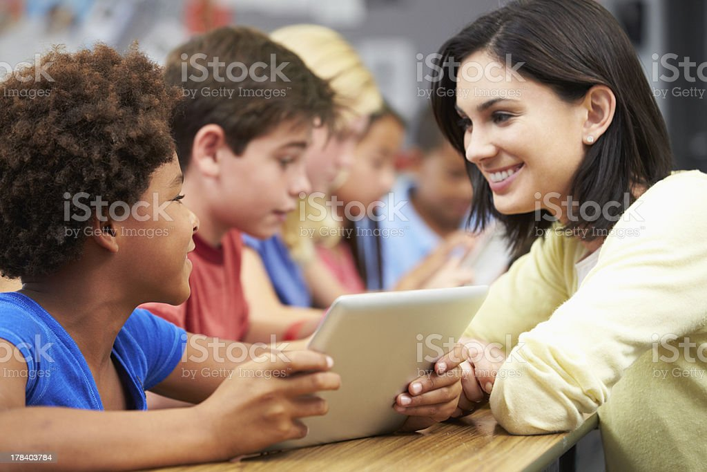 Pupils In Class Using Digital Tablet With Teacher stock photo