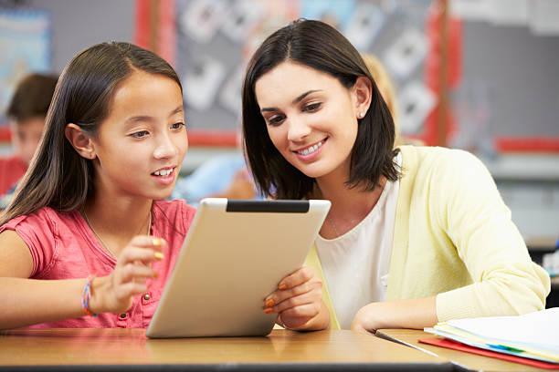 Schüler mit digitalen Tablet In Klasse mit Lehrer – Foto
