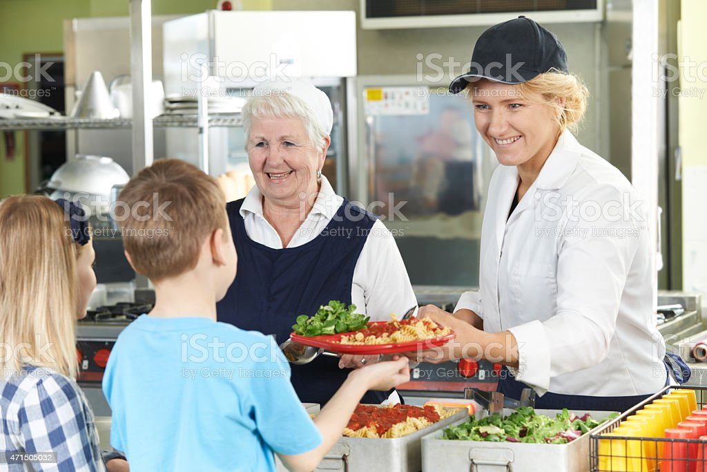 Pupils In School Cafeteria Being Served Lunch By Dinner Ladies stock photo