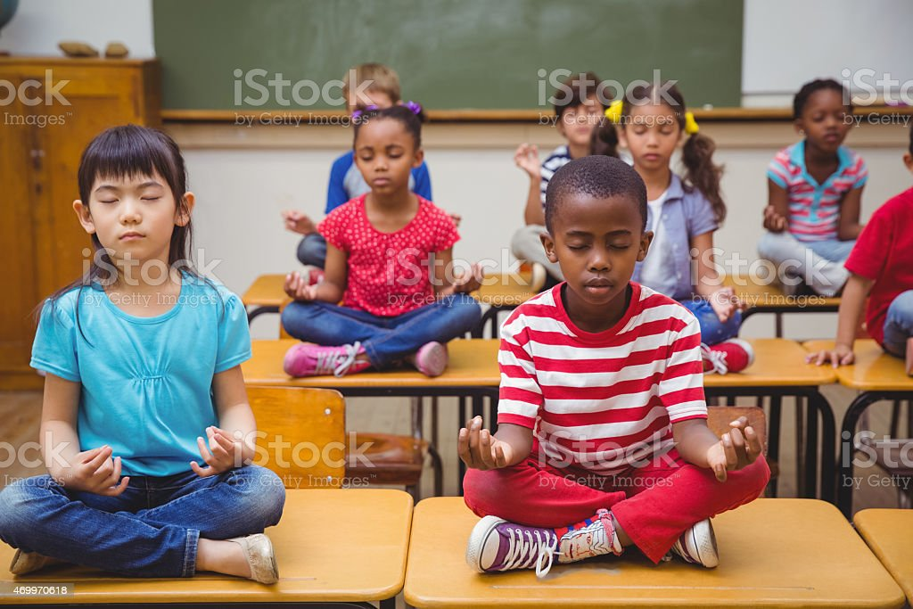 Pupils meditating in lotus position on desk stock photo