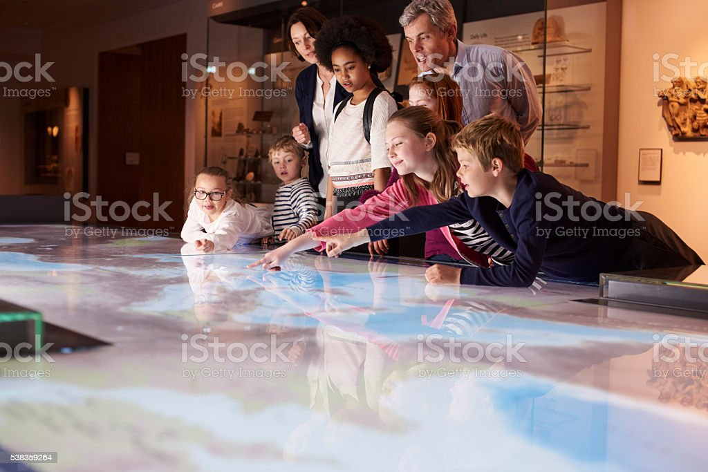 Pupils On School Field Trip To Museum Looking At Map stock photo