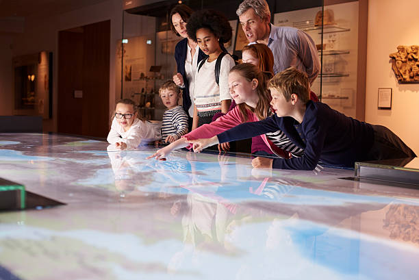 pupils on school field trip to museum looking at map - museum stockfoto's en -beelden