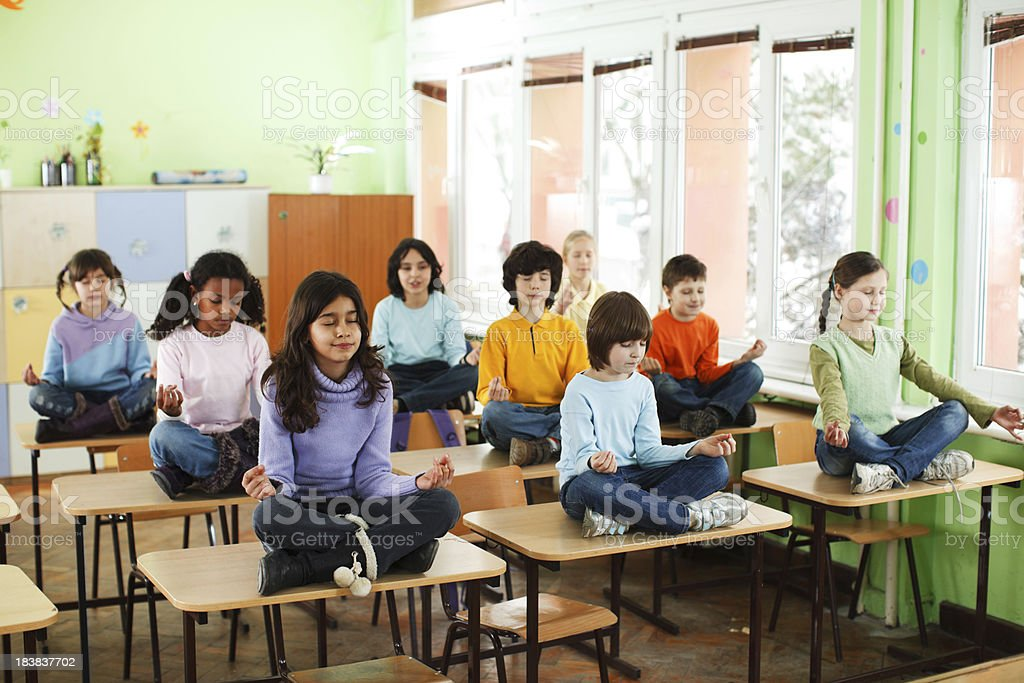 Pupils practicing yoga in the classroom. stock photo