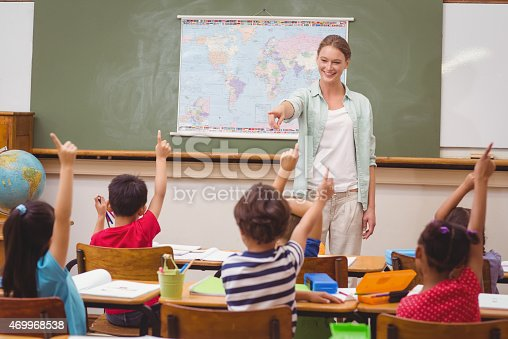 469968322 istock photo Pupils raising hand in classroom 469968538