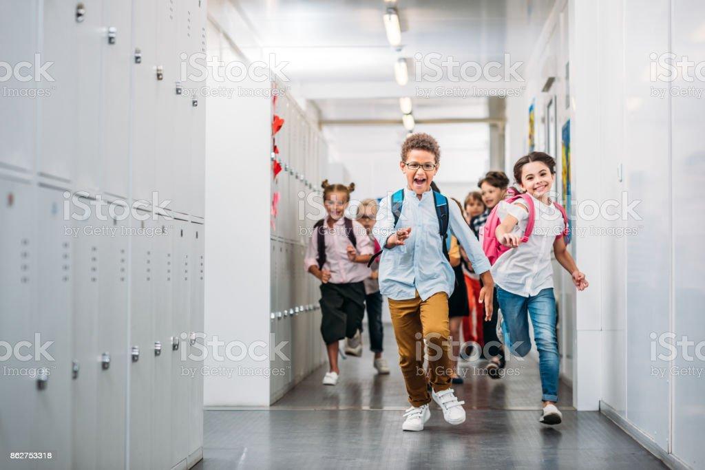 pupils running through school corridor cute funny pupils running through school corridor Adult Student Stock Photo