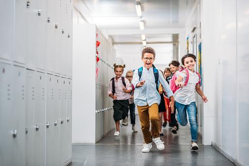 Pupils Running Through School Corridor Stock Photo - Download Image Now