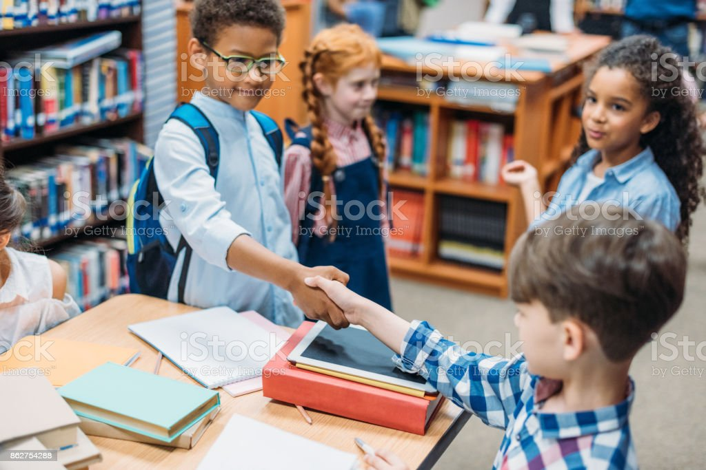 pupils shaking hands stock photo