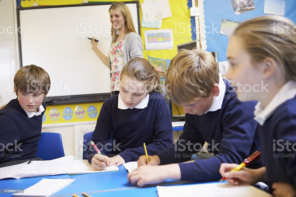 Pupils Sitting At Table As Teacher Stands By Whiteboard stock photo
