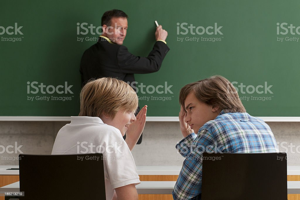 pupils whispering during lesson royalty-free stock photo