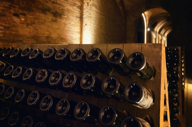 Pupitre and wine bottles inside an underground cellar Pupitre and bottles inside an underground cellar for the production of traditional method sparkling wines in italy cellar stock pictures, royalty-free photos & images
