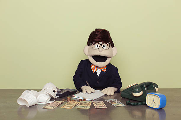 Puppet Accountant Counts American Dollars with Calculator A puppet accountant and financial advisor sits with American dollars ready to do business at his office desk. He is smiling while holding a pen and ready to grow your business. Dressed in business suit with bow tie. Retro styled. puppet stock pictures, royalty-free photos & images