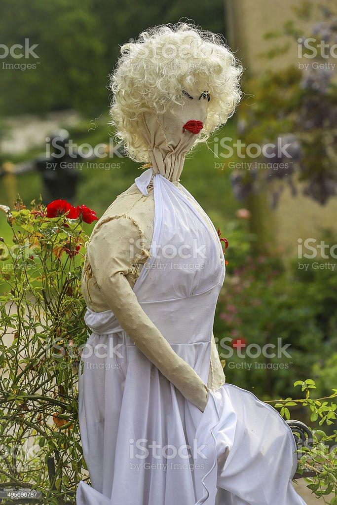 Puppet scarecrow in white dress and blonde hair red lipstick stock photo