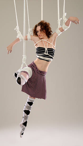 Puppet to Fashion; Woman Model Hanging, Suspended From White Ropes stock photo