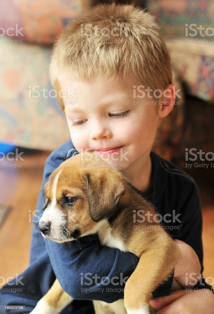 Puppy being held by a toddler boy royalty-free stock photo
