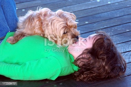 Little girl getting kisses and licks from her pet dog. Click to see more...