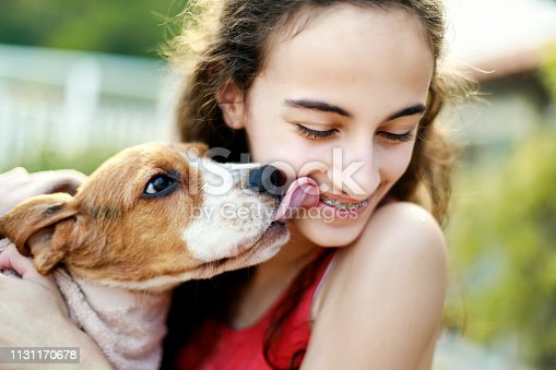 Puppy kissing teenage girl
