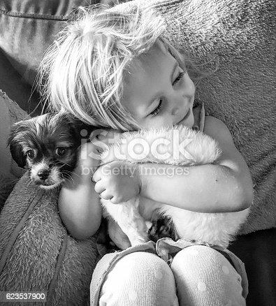 A young girl lovingly hugs her new puppy