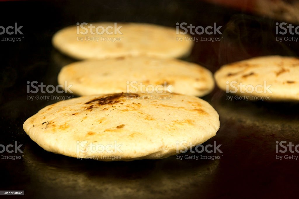 Pupusa on the griddle stock photo