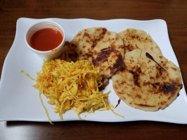 pupusa or tortilla stuffed with cheese on plate with cabbage and tomato sauce stock photo