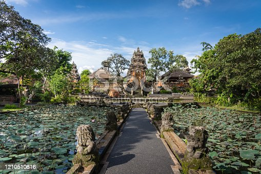 Way towards the famous and majestic Hindu Pura Taman Kemuda Saraswati Temple surrounded with a lotus pond in Ubud under blue summer sky, Ubud, Bali, Indonesia, South-East Asia.