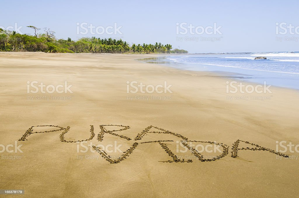 Pura Vida written on Costa Rican beach stock photo