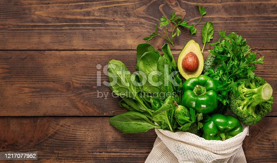 1126188273 istock photo Purchase healthy food. Top view shopping bag with healthy food clean eating. Green vegetable on wooden background top view 1217077952