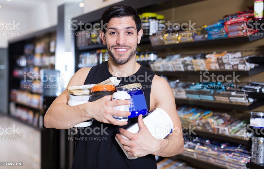 purchaser  holding stack of sport nutrition stock photo