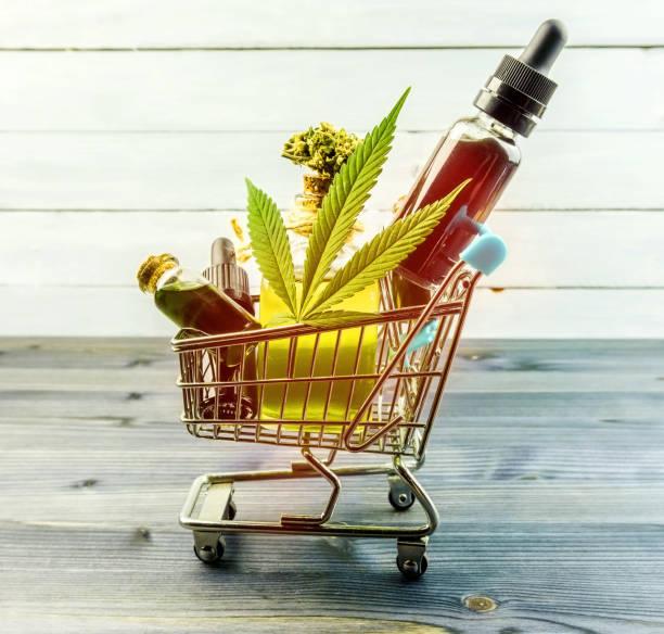 Purchasing Cannabis oil concept, Cannabis CBD oil bottles in miniature shopping cart stock photo