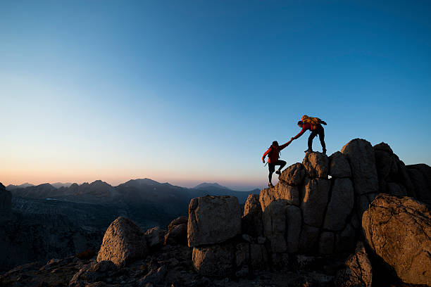 pure adventure Pair of climbers, one helping the other to the summit of a peak  taking the plunge stock pictures, royalty-free photos & images