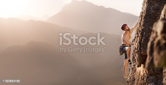 Shot of a young man climbing on a mountain with valley on the background