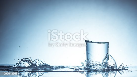 Pure drinking water with splashes in a round glass on a light green background close up