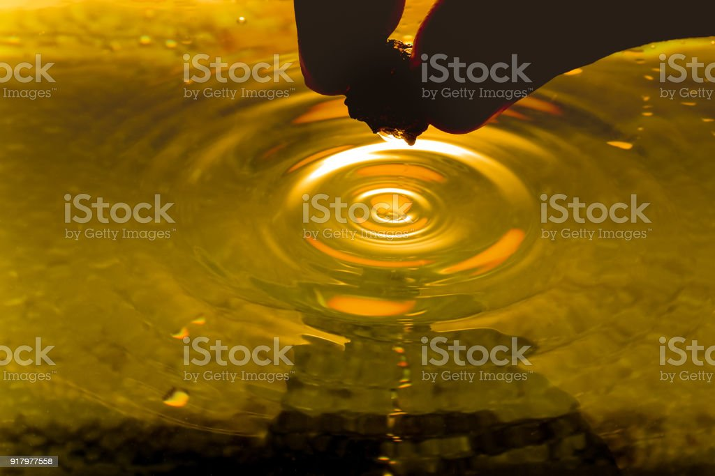 pure gold ore found in the mine is in the hands of men in the dark on liquid gold background stock photo