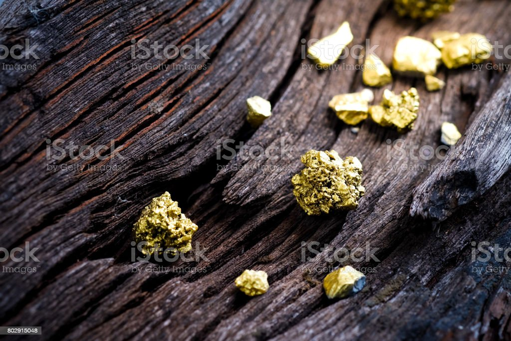 Pure gold ore on old wooden rails stock photo