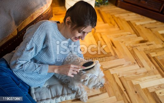 Teenage girl with hearing aid grooming and cuddling her dog